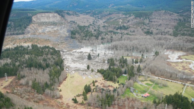 This image, released by the Washington State Department of Transportation, shows the hillside that gave way in the upper left. It also shows the blocked highway and river.