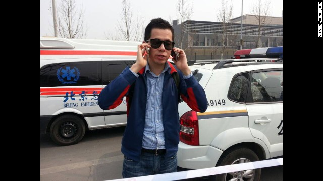"""On two phones in between a police car and an ambulance: coordinating live coverage from Beijing as families of MH370 protest in front of the Malaysian embassy."" By CNN's Steven Jiang, Beijing, March 25. Follow Steven on Instagram at instagram.com/stevencnn."