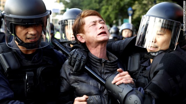 Riot police detain a protester near the Cabinet compound on March 24.