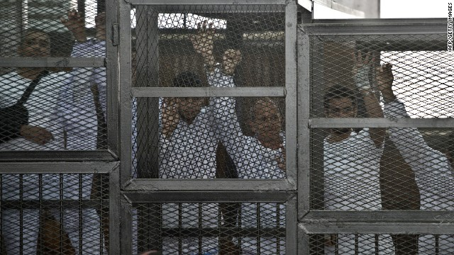 File photo: Australian journalist Peter Greste (C) of Al Jazeera and his colleagues stand inside the defendants cage during their trial for allegedly supporting the Muslim Brotherhood.