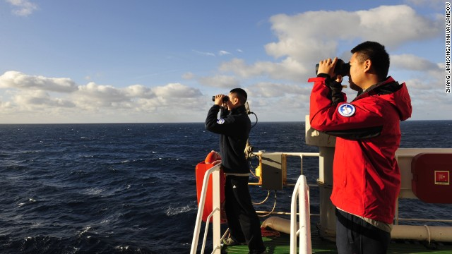Crew members of the Chinese icebreaking ship Xuelong scan the Indian Ocean during a search for the missing jet on Wednesday, March 26.