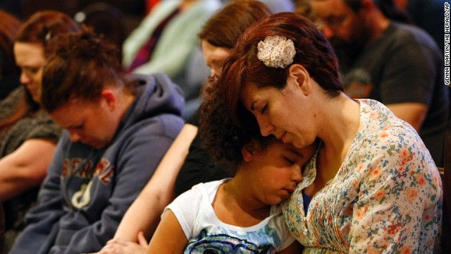 Natalie Reed, right, and her 5-year-old daughter, Deja, attend a prayer service at Arlington United Church on March 24 for those affected by the landslide.