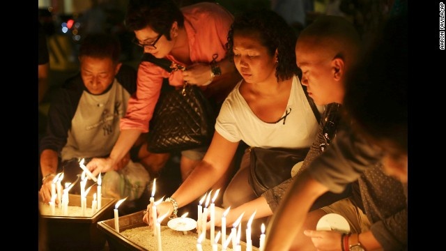 People in Kuala Lumpur light candles during a ceremony held for the missing flight's passengers on March 27.