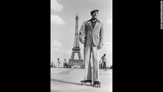 "Gene Kelly wears roller skates in Paris while shooting scenes for ""That's Entertainment, Part II."""