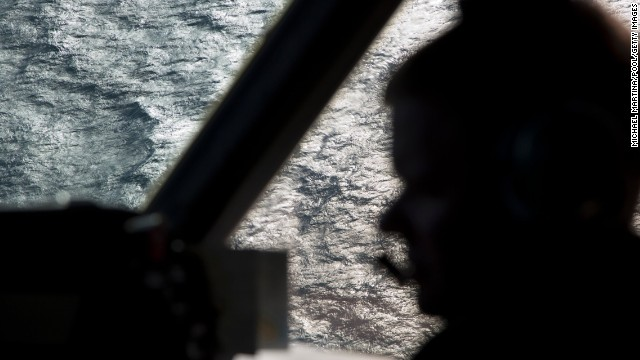 A member of the Royal Australian Air Force is silhouetted against the southern Indian Ocean during the search for the missing jet on Thursday, March 27.