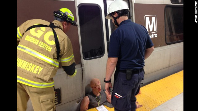Responders work at the scene of a mock subway accident.
