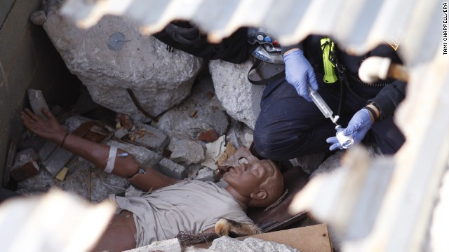 A Task Force member works on a dummy victim during a mock steel building collapse.