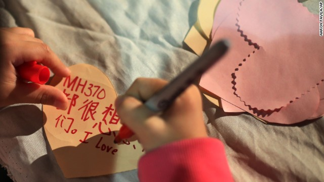 A girl in Kuala Lumpur writes a note during a ceremony for the missing passengers on March 30.