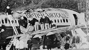 Firemen examining the wreckage of a British Airtours 747 that burst into flames at Manchester Airport.