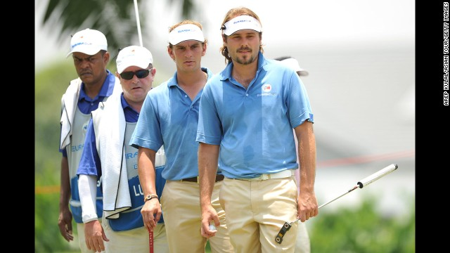 From right, Victor Dubuisson, Joost Luiten and their Team Europe caddies are seen on the first day of the EurAsia Cup on Thursday, March 27, in Kuala Lumpur, Malaysia.