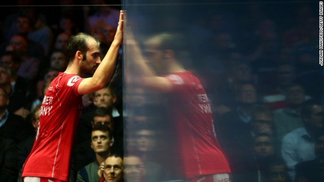 Simon Rosner wipes his hand on the glass sidewall Wednesday, March 26, during the quarterfinals of the Canary Wharf Squash Classic in London.