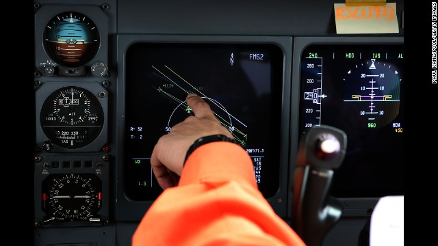 A member of the Japanese coast guard points to a flight position data screen while searching for debris from the missing jet on Tuesday, April 1.