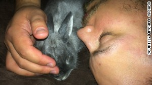 Mitchell Casado snuggles with his rescue rabbit, Buddy.