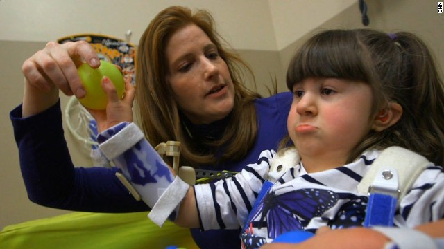 "Four-year-old Hannah Mohn uses a ""robotic exoskeleton"" to help lift her arms."