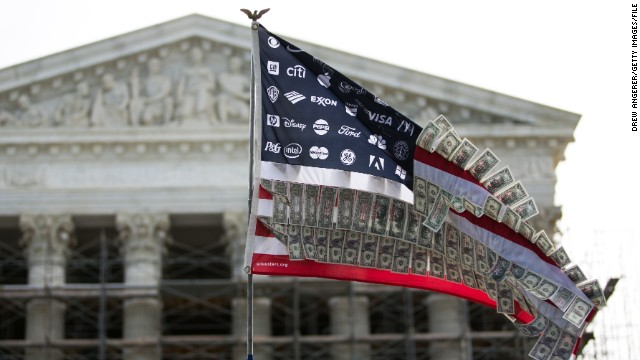 A flag adorned with corporate logos and fake money flies at a rally against money in politics in front of the Supreme Court.