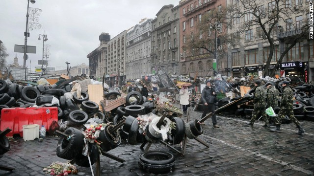 People pass by barricades near the Dnipro Hotel in Kiev on April 1.