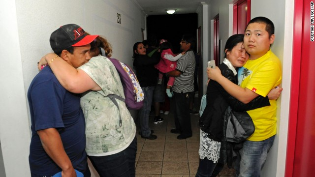 People embrace on the upper floor of an apartment building in Iquique on April 1.