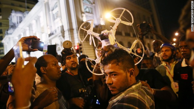 Protesters question a man who was operating a quadcopter drone with camera during February's protests in Rio.