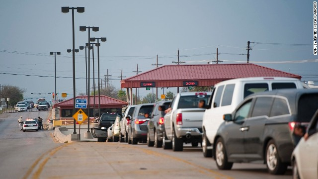 Vehicles wait at a closed entrance to Fort Hood.