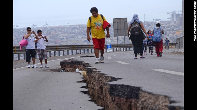 People walk along a cracked road in Iquique on Wednesday, April 2.