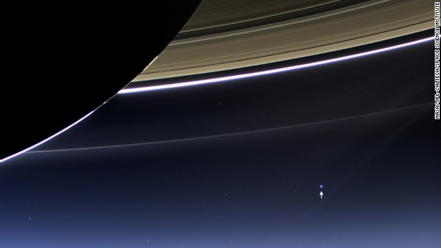 The small bright dot seen in the bottom right is not another Saturn moon. It's Earth. The distance between Saturn and our planet is constantly changing because both are constantly in motion. When they are closest together during their orbits, Saturn is 746 million miles away from Earth. At its farthest, they are just over a billion miles apart.