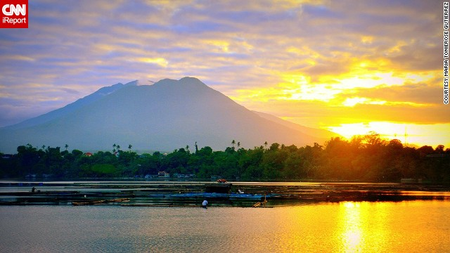 "The sun rises peacefully above Sampaloc Lake in San Pablo, Philippines. ""It was one of those moments when the world seems still half asleep and everything is at peace,"" said Maria Tonierose Gutierrez of her hometown."