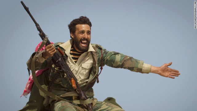 A Libyan rebel urges people to leave as shelling from Moammar Gadhafi's forces started landing outside of Bin Jawad, Libya, in March 2011.
