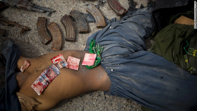 Following an attack Wednesday, March 12, on the former Afghan intelligence headquarters in Kandahar, Pakistani bank notes are displayed on the body of a dead suicide bomber after police found them in his pocket.
