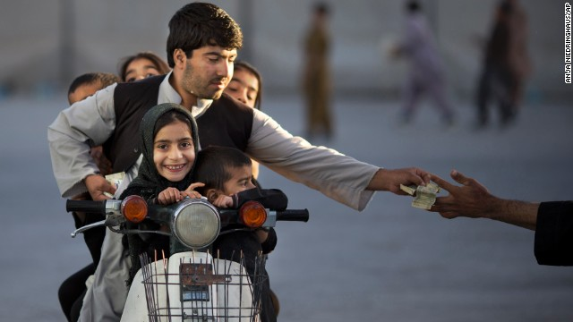 Niedringhaus had worked in the region for over 20 years. In this photo, she shows an Afghan man with his five children on his motorbike, paying money to enter a park in Kandahar.