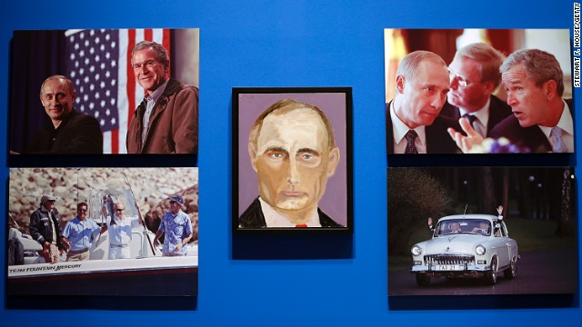 "A portrait of Russian President Vladimir Putin, painted by George W. Bush, is displayed between photographs as part of the library's exhibit ""The Art of Leadership: A President's Personal Diplomacy."" The exhibit includes more than two dozen never-before-seen portraits by Bush."
