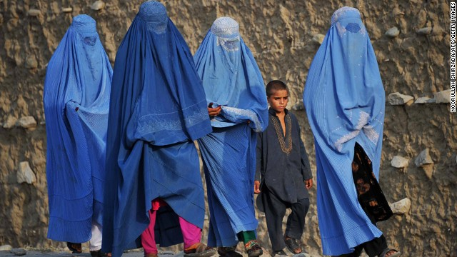 "Covered from head to toe, women walk on the outskirts of Jalalabad, accompanied by a liberally-dressed boy, in October 2013. Horia Mosadiq, Amnesty International's Afghanistan Researcher, says that although there are not any legal restrictions on women's dress code in Afghanistan, considerable social and cultural pressures force them to wear a burqa or fully cover themselves. ""They would simply be targeted otherwise,"" she says, ""by the Taliban, their family members, or even passers-by on the street."""
