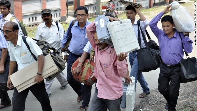 Poll officials carry voting machines in Nagaon, Assam, on Sunday in preparation for the national election.