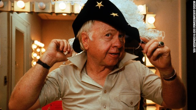 "Rooney tries on a feathered hat in his dressing room during a run of the play ""Sugar Babies"" in October 1979. He was nominated for a Tony for the role."