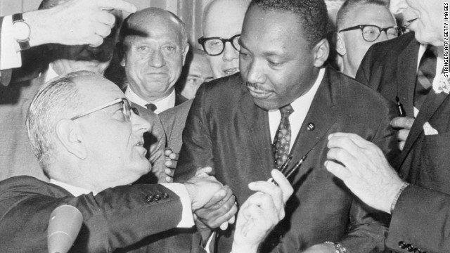 After signing <a href='http://www.cnn.com/2014/04/10/politics/civil-rights-act-interesting-facts/'>the Civil Rights Act of 1964</a>, U.S. President Lyndon B. Johnson shakes hands with the Rev. Martin Luther King Jr. The legislation outlawed discrimination in public places and banned discrimination based on race, gender, religion or national origin. It also encouraged the desegregation of public schools.