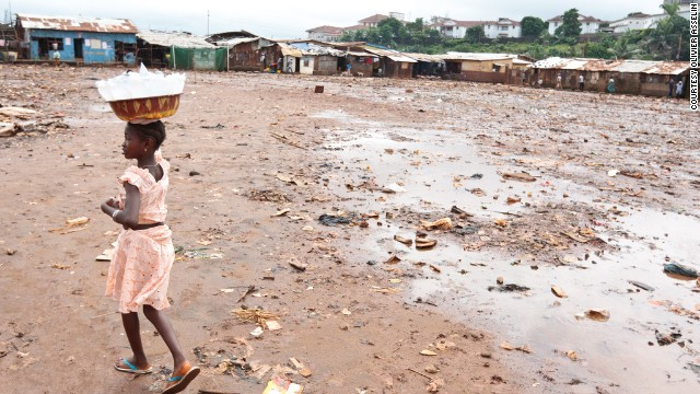 People living in poverty, without access to clean water and sanitation have the highest risks of infection with intestinal worms. A girl carries plastic bags of drinking water she sells in the Kroo bay slum of Freetown, Sierra Leone.