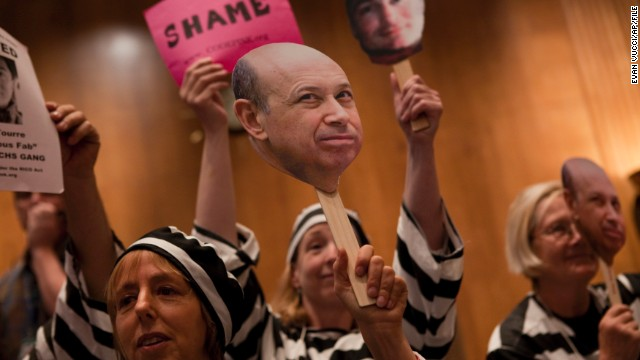 "Today, the top 1% controls about 40% of national wealth. At a hearing in Washington D.C. about Wall Street and the financial crisis, protesters hold a placard depicting Goldman Sachs CEO Lloyd Blankfein, who once famously said, ""I'm doing God's work."""