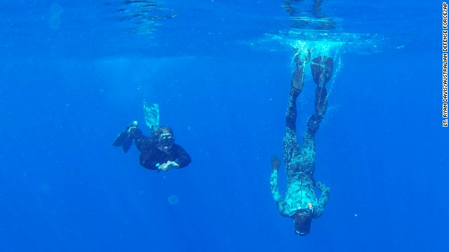 Australian Defense Force divers scan the water for debris Monday, April 7, in the southern Indian Ocean.