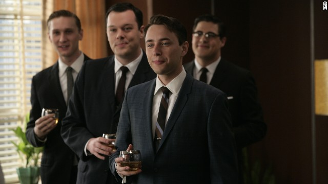 "Wearing dark, formal suits was a nearly century-old tradition by the time ""Mad Men"" ad men donned identical looks -- with highballs -- at the Sterling Cooper agency in 1960. Their suits' slim silhouettes came from the returning WWII soldiers' athletic figures, said University of Notre Dame history professor and author Linda Przybyszewski. Suits narrowed in the shoulders, torso and legs to fit the new physique."