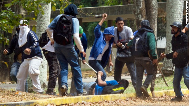 An opposition student struggles with members of a pro-government group at the Central University of Venezuela in Caracas on April 3.