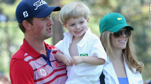 Webb Simpson , who won the U.S. Open in 2012, holds his son James as his wife Dowd looks on at the action.