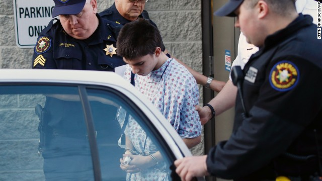 Accused attacker Alex Hribal, 16, is escorted from a district magistrate after he was arraigned as an adult on April 9. He faces four counts of attempted homicide, 21 counts of aggravated assault and one count of possession of a weapon on school grounds, according to a criminal complaint made public.