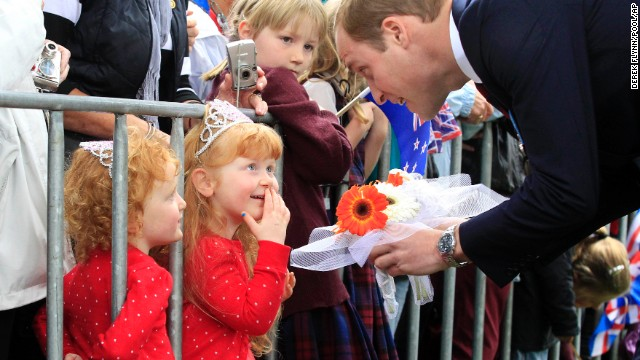 Prince William greets 3-year-old twins Lola and Milly Barnett after a wreath-laying ceremony in Blenheim.