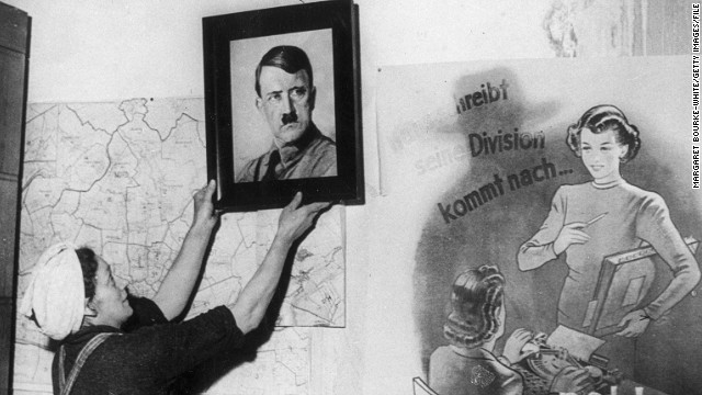 """It's not an easy profession and by and large it requires a huge amount of personal sacrifice,"" said Brooks. ""From a historical perspective, Margaret Bourke-White was always a source of inspiration because she was such a pioneer."" In this photo by Bourke-White, a woman removes a portrait of Hitler from the wall of a protestant church in Frankfurt at the end of World War Two."