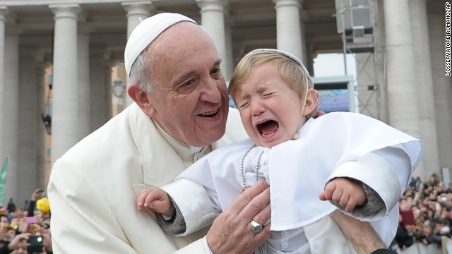 Daniele De Sanctis, a 19-month-old child dressed up as a pope, is handed to Francis as the pontiff is driven through the crowd February 26 at St. Peter's Square in the Vatican.