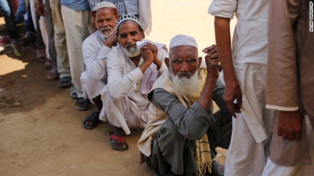 Indian Muslims wait outside a polling booth to cast their votes on Thursday, April 10.