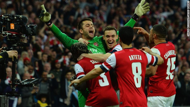 Arsenal players mob goalkeeper Lukasz Fabianski after the Gunners beat Wigan on penalties in the FA Cup.