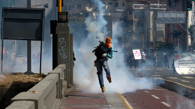 A masked anti-government demonstrator throws a tear gas canister back at Bolivarian National Police during clashes in Caracas on Saturday, April 12.