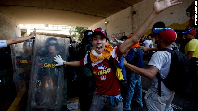 A protester shouts for fellow demonstrators to not attack the Bolivarian National Police troops trapped under a highway with protesters during clashes on April 12.