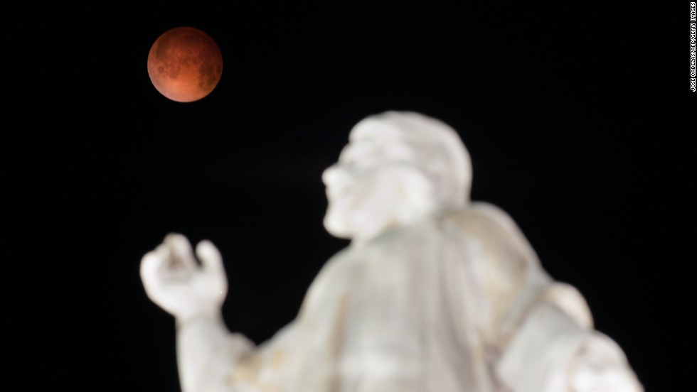 "A ""blood moon"" rises over the El Salvador del Mundo monument in San Salvador early Tuesday, April 15, as a total lunar eclipse attracts sky gazers across the Americas. In a total lunar eclipse, the full moon turns a coppery red as it passes into Earth's shadow. ""It's like seeing all the sunsets on Earth projected on the moon at once,"" says Indra Petersons of CNN's ""New Day."""