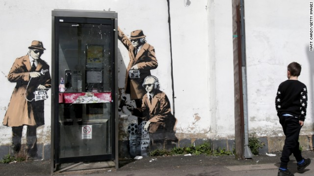 A boy walks past graffiti street art on Monday, April 14, believed to be by Banksy. The image depicts men in trench coats and dark glasses holding old-fashioned listening equipment -- apparently a commentary on government surveillance. The artwork appeared on the side of a house in Cheltenham near the Government Communications Headquarters, the U.K. equivalent of the National Security Agency.